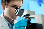 Scientist looks into microscope — Stock Photo