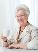 Senior woman with a cup of coffee — Stock Photo