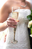 The hand of the bride holds a beautiful glass with champagne — Stock Photo