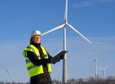 Engineer or architect with white safety hat and wind turbines on — Stock Photo