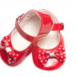 Isolated small white dappled red baby shoes on white — Стоковая фотография
