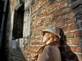 Dreaming pretty woman with white hat in a romantic alley — Stock Photo