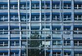 Kommunist kontorsbyggnad återspeglas i windows till modern kontorsbyggnad — Stockfoto