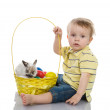 Funny little boy and Easter rabbit inside a basket full of easter eggs — Stock Photo