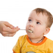 Stock Photo: Mother feeding her baby by spoon