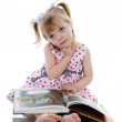 The dreaming baby girl reading a book. — Stock Photo