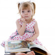 Stock Photo: Dreaming baby girl reading book