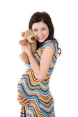 Beautiful pregnant woman holding toy in anticipation of playing with her baby. — Stock Photo