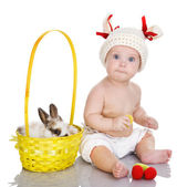 Baby girl and little easter bunny inside a basket. — Stock Photo