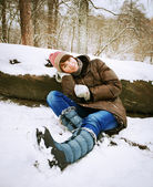 Winter girl in the forest sitting in the snow. — Stock Photo