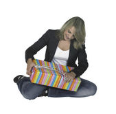 Sitting girl unpacking a present — Stock Photo