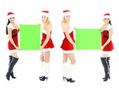 Christmas girls holding green blank banner — Stock Photo