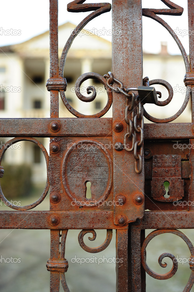 Old and rusty gate with chain and padlock — Stock Photo #9448094