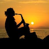 Mulher tocando saxofone ao pôr do sol — Fotografia Stock