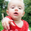 Year-old girl eating raspberries - Stock Photo