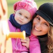 Smiling mother and child playing on the swing — Stock Photo #9135135