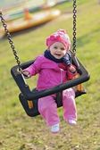 Happy baby playing with the swing — Stock Photo