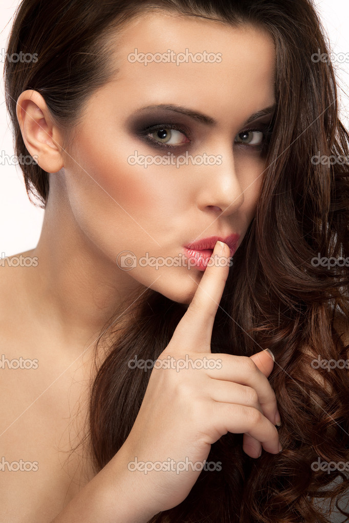 A portrait of a beautiful brunette with a finger on her lips showing to keep silence, hush — Stock Photo #8779800
