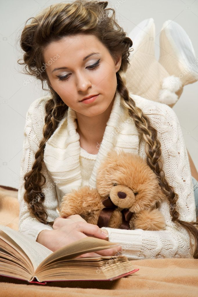 Young girl reading book lying on the floor with toy — Stock Photo #8477660