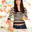 Stock Photo: Girl with hand painted in colorful paints ready for hand prints