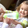 Young girl feeds her baby sister in a highchair - Stock Photo