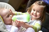 Young girl feeds her baby sister in a highchair — Stock Photo