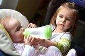 Jovem alimenta a irmã bebê em uma cadeira de papa — Fotografia Stock