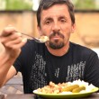 Portrait of a man eating outdoor — Stock Photo