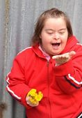 Down syndrome woman blowing dandelion — Stock Photo