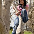 Girl sitting back on tree — Stock Photo