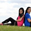 Two young beautiful girls sitting on a background of green nature — Stock Photo