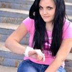 A cute teenage girl sitting on the bleacher steps — Stock Photo #10229535