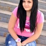 A cute teenage girl sitting on the bleacher steps — Stock Photo #10229537