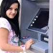 Royalty-Free Stock Photo: Woman withdrawing money from credit card at ATM.