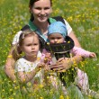 Mother with her two daughters on meadow — Stock Photo #10586888