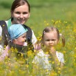 Mother with her two daughters on meadow — Stock Photo #10586898
