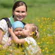 Mother with her two daughters on meadow — Stock Photo
