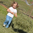 Baby girl playing with cut grass - Lizenzfreies Foto