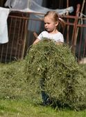 Baby girl playing with cut grass — Stock Photo