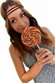 Nice girl looks on lolipop — Stock Photo