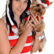 Pretty girl and dog in santa hat at Christmas — Stock Photo #8029179