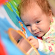 Happy baby playing in baby gym toy — Stock Photo