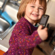 Little girl speaking by cell phone, white background — Stock Photo #8573435