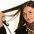 Portrait of young beautiful girl doing hairstyle with hair iron — Stock Photo