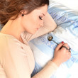 Portrait of young beautiful woman with jewerly in bed — Stock Photo