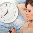 Young sleeping woman and alarm clock in bedroom at home. — Stock Photo