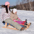 Mother sits on sled in park with child at winter — Stock Photo