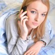 Attractive young woman talking on the phone while lying in the bed.  — Stock Photo