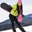Woman with snowboard standing on top of snowy mountain — Stock Photo