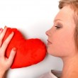 Attractive young woman hugging heart-shaped pillow. All on white background — Stock Photo